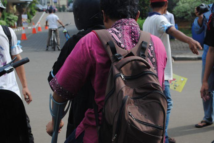 Mengantarkan mahasiswa ke fakultas dengan jasa ojek vespa