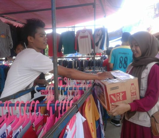 Pedagang sedang memberikan donasinya ke dalam kotak donasi melalui volunteer yang sedang menggalang dana untuk korban bencana Tsunami Selat Sunda. Kegiatan Berlangsung di Pasar Pagi kampus II UIN Jakarta pada 30 Desember 2018.